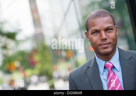 A young man in a business suit with a blue shirt and red tie. On a city street. - Stock Photo