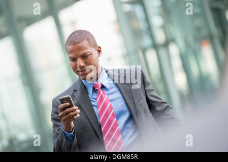A young man in a business suit with a blue shirt and red tie. On a New York city street. Using a smart phone. - Stock Photo