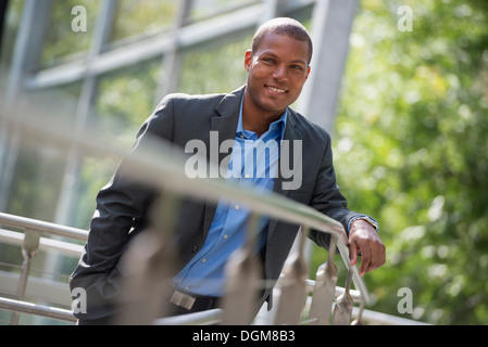A young man in a jacket and open collared blue shirt, leaning on a railing in a city park in summer. Looking at - Stock Photo