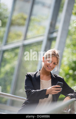 A young blonde businesswoman on a New York city street. Wearing a black jacket. Using a smart phone. - Stock Photo