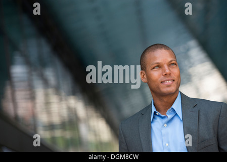A businessman in a suit, with his shirt collar unbuttoned. On a New York city street. - Stock Photo