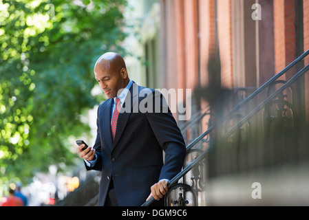 Business people. A businessman in a suit and red tie, checking his phone. - Stock Photo
