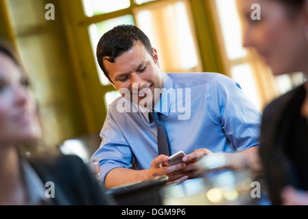Business people. Three people around a cafe table, one of whom is checking their phone.