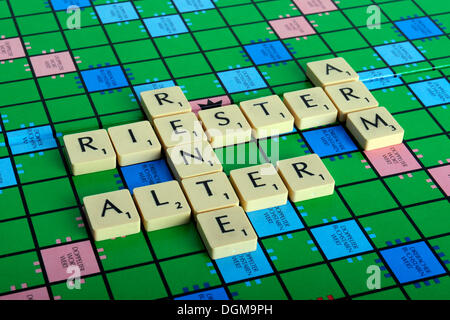 Scrabble letters forming the words Riester, Rente, arm and Alter, German for the Riester pension and being poor - Stock Photo