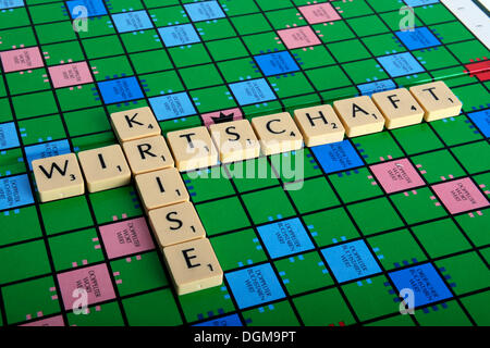 Scrabble letters forming the words Wirtschaft and Krise, German for economic crisis - Stock Photo