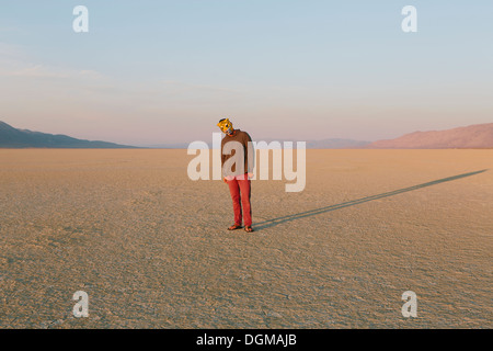 The landscape of the Black Rock Desert in Nevada. A man wearing an animal mask. Casting a long shadow on the ground. - Stock Photo