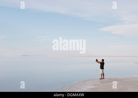 A man standing at edge of the flooded Bonneville Salt Flats at dusk, taking a photograph with a tablet device, near - Stock Photo