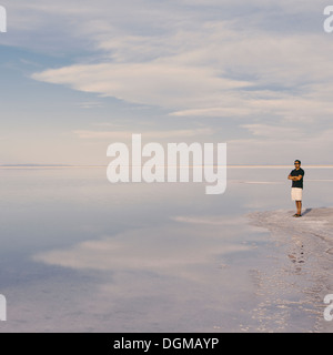 A man standing at edge of the flooded Bonneville Salt Flats at dusk. Arms folded. - Stock Photo