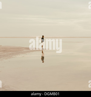 A man standing at the edge of the flooded Bonneville Salt Flats at dusk. - Stock Photo