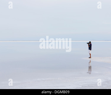 A man standing on the edge of the flooded Bonneville Salt Flats, taking a photograph at dusk. - Stock Photo