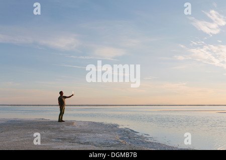 A man standing at edge of the flooded Bonneville Salt Flats at dusk, taking a photograph with a tablet device. - Stock Photo