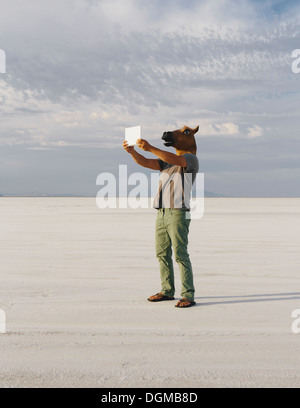 A man wearing a horse mask, taking a photograph with a tablet device, on Bonneville Salt Flats. - Stock Photo