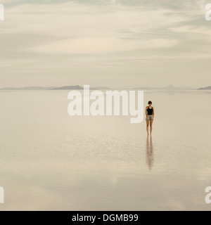 Woman standing on the flooded Bonneville Salt Flats, at dusk. - Stock Photo