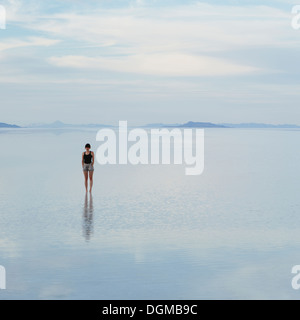 A woman standing on the flooded Bonneville Salt Flats, at dusk. - Stock Photo