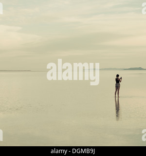 A woman standing on the flooded Bonneville Salt Flats, taking a photograph with a smart phone. - Stock Photo