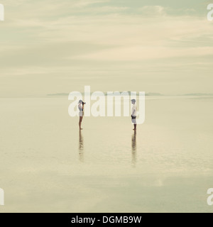 Man and woman standing on the flooded Bonneville Salt Flats, taking photographs of each other at dusk. - Stock Photo