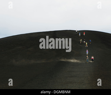A black volcanic cone hillside in Craters of Moon national monument preserve in Butte County Idaho People walking - Stock Photo