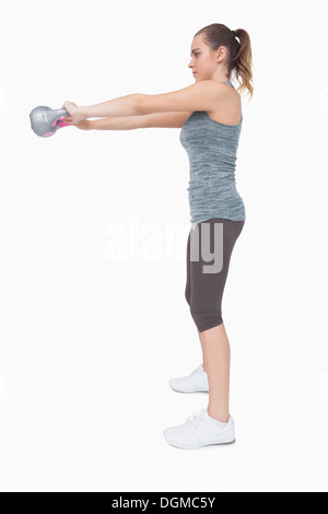 Young woman working with a kettle bell - Stock Photo