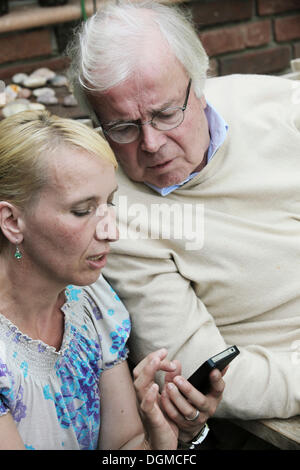 Young woman explaining a smartphone to an elderly man - Stock Photo
