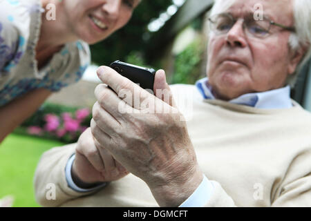 Young woman explaining to a senior citizen how to use a smartphone - Stock Photo