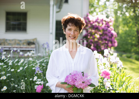 Organic farm. Summer party. A woman holding a bunch of flowers. - Stock Photo
