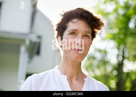 Organic farm. Summer party. A mature woman smiling. - Stock Photo