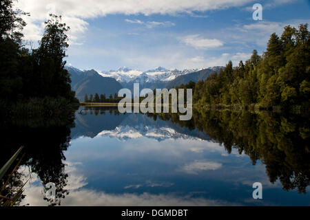 The Southern Alps with Mt. Cook and Mt. Tasman reflected in the waters of Lake Matheson, West Coast, South Island, - Stock Photo