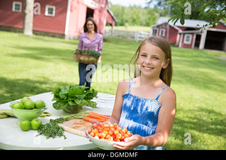 Family party. A child carrying a bowl of fresh picked cherries to a buffet table. - Stock Photo