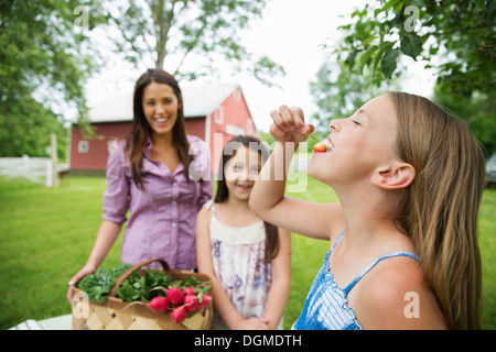 Family party. Two young girls standing by a table, one eating a fresh ripe cherry. A young woman carrying a bowl - Stock Photo