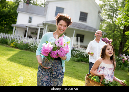 Family party. Parents and children walking carrying flowers, fresh picked vegetables and fruits. Preparing for a - Stock Photo
