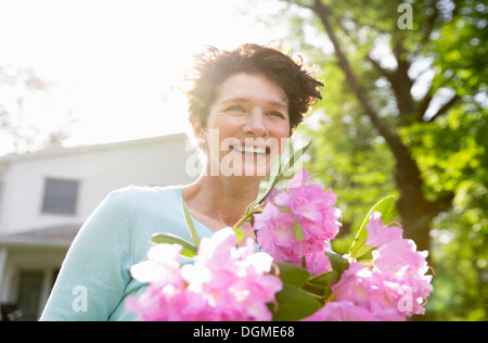 Family party. A woman carrying a large bunch of rhododendron flowers, smiling broadly. - Stock Photo