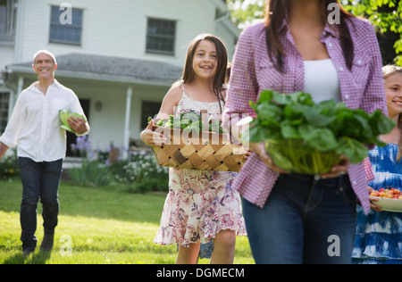 Family party. Parents and children carrying flowers, fresh picked vegetables and fruits. Preparing for a party.