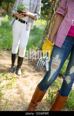 Two young girls in working clothes, one in rubber gloves holding gardening tools, and one holding a plant in a pot. - Stock Photo