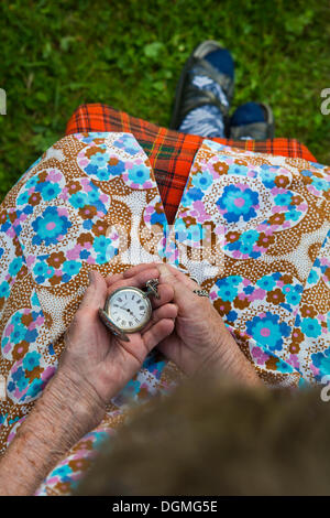 Elderly woman holding an old pocket watch in her hands - Stock Photo