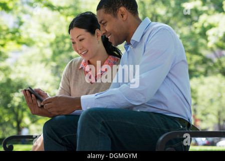 Summer. Business people. A man and woman sitting on a bench, using a smart phone. - Stock Photo