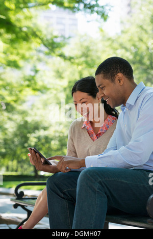 Summer. Business people. A man and woman sitting using a digital tablet, keeping in touch. - Stock Photo
