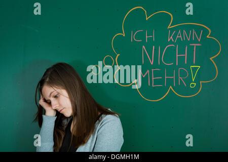 Depressed looking teacher standing in front of the blackboard with a speech bubble, 'Ich kann nicht mehr', German - Stock Photo