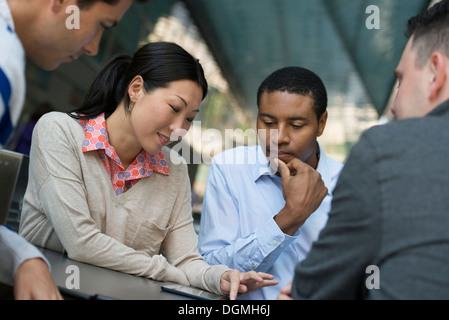 Business people on the move. Four people gathered around a digital tablet having a discussion. - Stock Photo