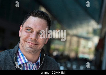 Business people on the move. A man in a open necked shirt and jacket. - Stock Photo