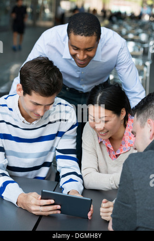 Business people on the move. Four people gathered around a digital tablet having a discussion. Overhead view. - Stock Photo