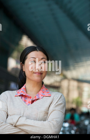 Business people on the move. A woman in a pink shirt and beige sweater. - Stock Photo