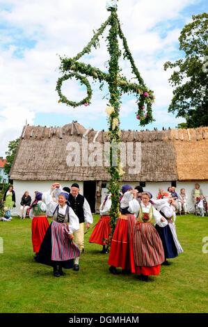 Dance around maypole, typical celebration of midsummer in Sweden, Tomelilla, Skåne, Sweden, Europe - Stock Photo