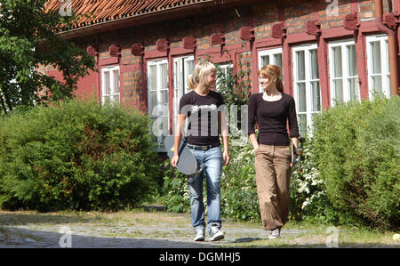 Two young girls, 15 years, walking in front of an old house, Ystad, Sweden, Europe - Stock Photo