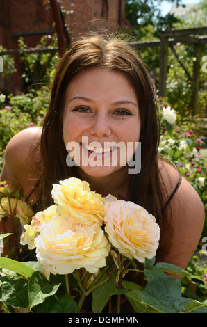 Young woman with roses in the rosegarden in Ystad, Sweden, Europe - Stock Photo