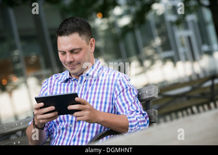 Summer in the city. A man sitting on a bench using a digital tablet. - Stock Photo