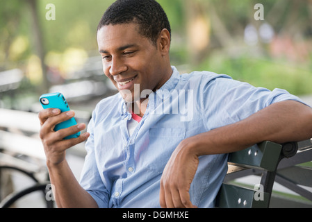 Summer in the city. A man sitting on a bench using a smart phone. - Stock Photo