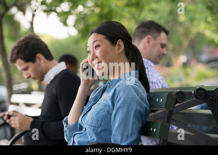 Summer in the city. One woman and three men sitting in the park, each on their own phone or using a tablet. - Stock Photo