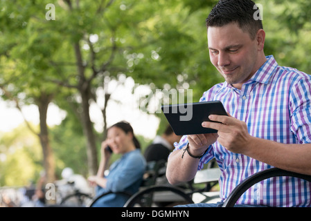 Summer. One woman and two men sitting in the park, each on their own phone or using a tablet. - Stock Photo