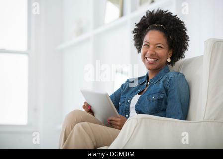 A young woman sitting in an armchair with a digital tablet. - Stock Photo