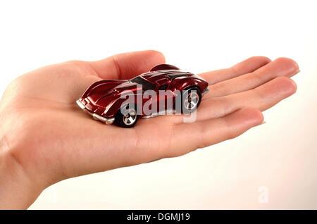 Hand holding a miniature car - Stock Photo